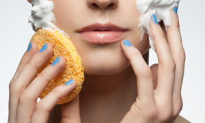 Portrait of young beautiful woman with sponge washing her face